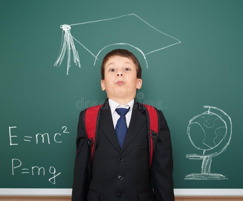 Σχολικό αγόρι με την ακαδημαϊκή ΚΑΠ στοκ εικόνα