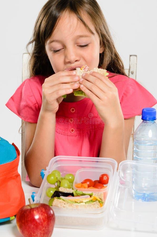Σχολικό κορίτσι που τρώει το συσκευασμένο σάντουιτς μεσημεριανού γεύματός της στοκ φωτογραφία με δικαίωμα ελεύθερης χρήσης