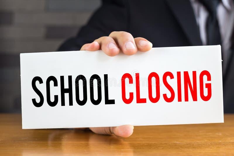 Σχολικό κλείσιμο, μήνυμα στην άσπρη κάρτα και λαβή κοντά στοκ εικόνα με δικαίωμα ελεύθερης χρήσης