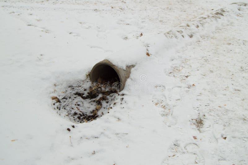 Σωλήνας αγωγών υπονόμων τσιμέντου, μια τρύπα με τα φύλλα και ρύπος, που καλύπτεται με το πρώτο χιόνι στοκ φωτογραφία με δικαίωμα ελεύθερης χρήσης