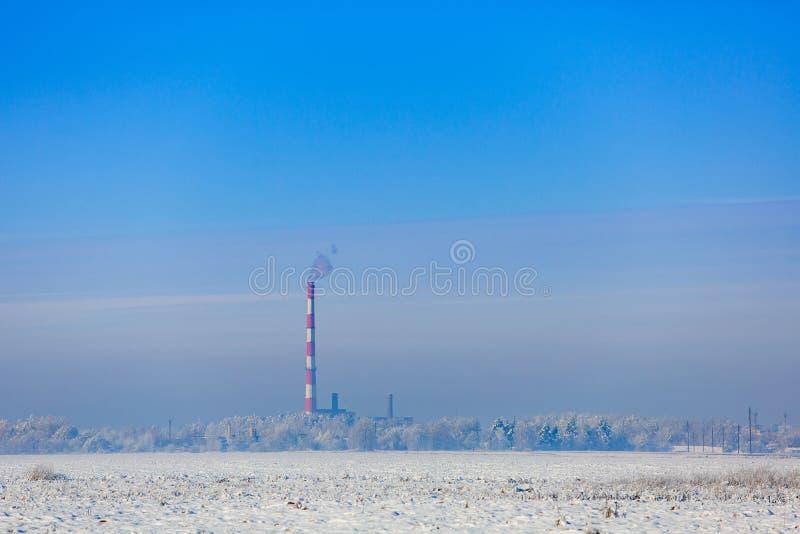 Σωλήνας εργοστασίων που απελευθερώνει τον καπνό στον παγωμένο αέρα οικολογικά προβλήματα στοκ εικόνες