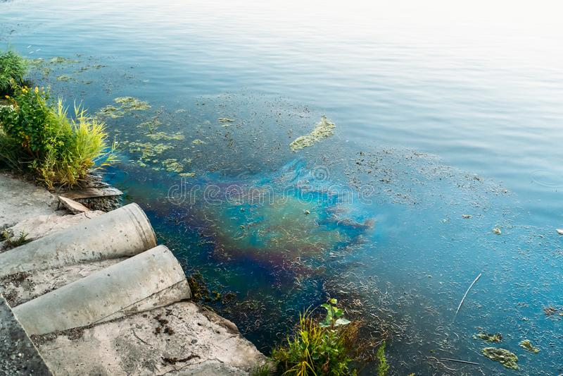 Σωλήνες υπονόμων στην ακτή, το λεκέ του πετρελαίου ή τα καύσιμα στην επιφάνεια νερού, μόλυνση φύσης από τις τοξικές χημικές ουσίε στοκ φωτογραφία με δικαίωμα ελεύθερης χρήσης