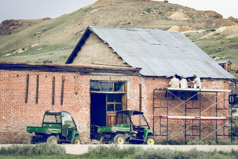 ΣΩΜΑ, ΚΑΛΙΦΟΡΝΙΑ: Ένα πλήρωμα οικοδόμησης αποκαθιστά τη ζημία στεγών σε ένα εγκαταλειμμένο ιστορικό κτήριο στη πόλη-φάντασμα στοκ εικόνες