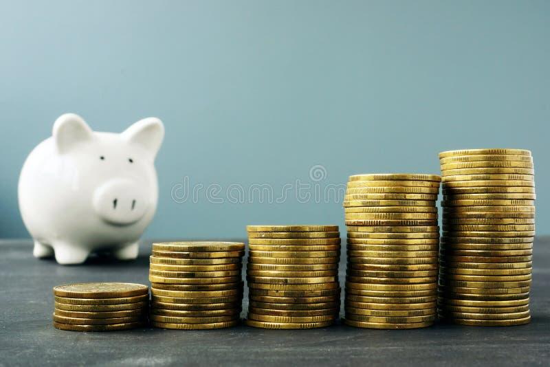 Σωροί νομισμάτων και piggy τράπεζα Αύξηση πλούτου και σχέδιο αποχώρησης στοκ εικόνες με δικαίωμα ελεύθερης χρήσης