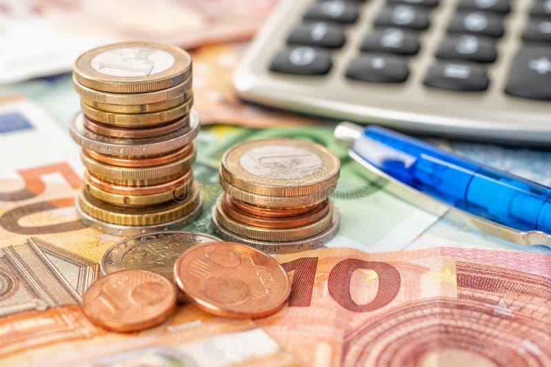 Σωροί νομισμάτων στους ευρο- λογαριασμούς με τον υπολογιστή στοκ εικόνες