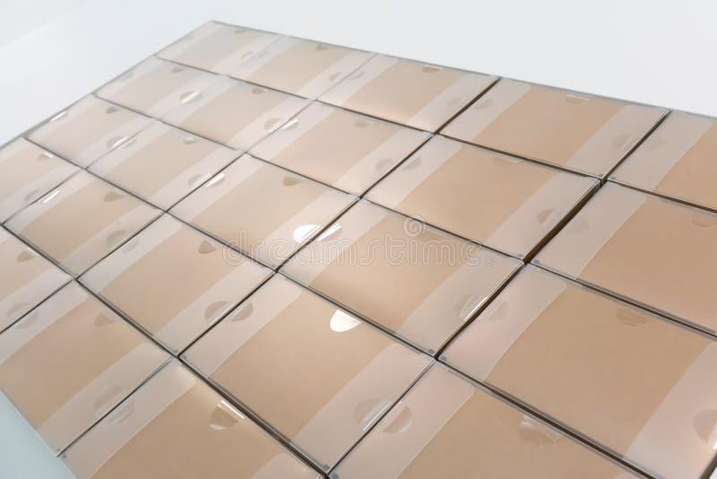 Σωροί των ανακυκλωμένων κιβωτίων εγγράφου στις σειρές μετά από τον έλεγχο περασμάτων και το τ στοκ εικόνες