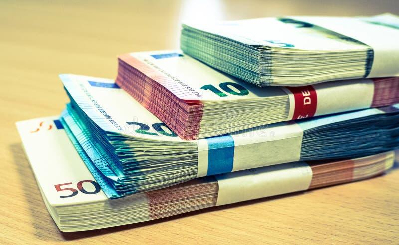 Σωροί των ευρο- λογαριασμών σε ένα γραφείο πεύκων στοκ εικόνες