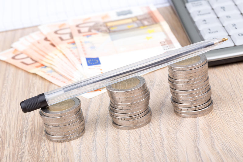 Σωροί των νομισμάτων που αυξάνονται σε μέγεθος με μια μάνδρα στους σωρούς στοκ φωτογραφία