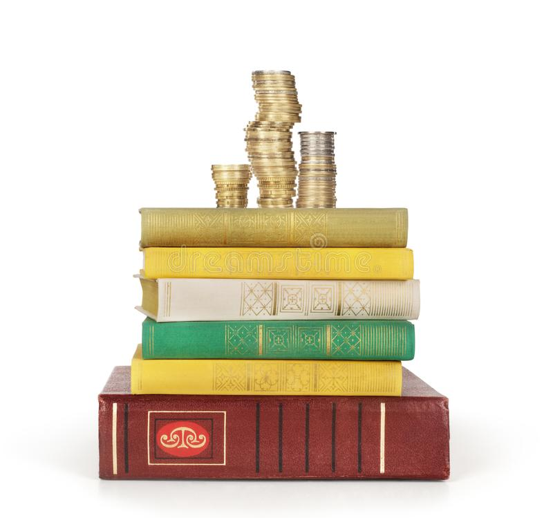 Σωροί των νομισμάτων σε έναν σωρό των βιβλίων στοκ εικόνα με δικαίωμα ελεύθερης χρήσης