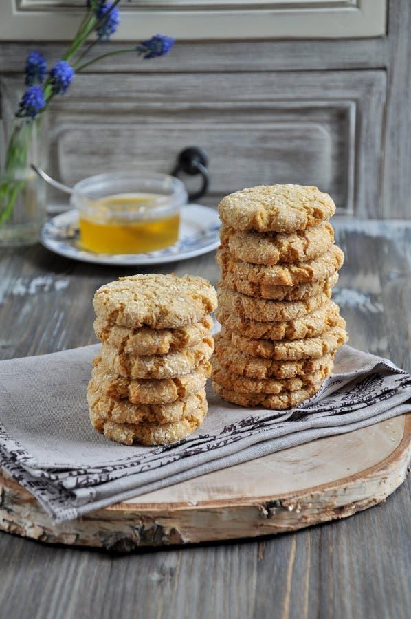 Σωροί των σπιτικών μπισκότων μελιού με τις ρωγμές που προστίθενται με την καρύδα στοκ φωτογραφία