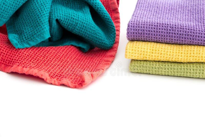 Σωρός ακατάστατου και σωρός των διπλωμένων ζωηρόχρωμων πετσετών κουζινών, στο λευκό στοκ εικόνα
