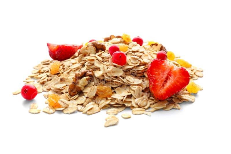 Σωρός ακατέργαστο oatmeal με τα ξύλα καρυδιάς και τα μούρα στο άσπρο υπόβαθρο στοκ φωτογραφίες