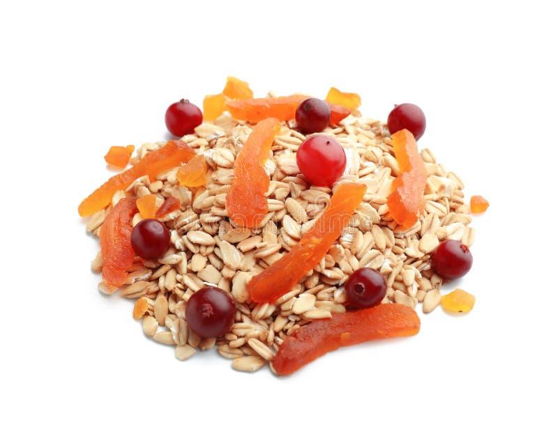 Σωρός ακατέργαστο oatmeal, του ξηρών βερίκοκου και των των βακκίνιων στο άσπρο υπόβαθρο στοκ εικόνα με δικαίωμα ελεύθερης χρήσης