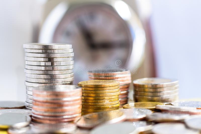 Σωρός νομισμάτων στο υπόβαθρο ρολογιών στοκ εικόνα με δικαίωμα ελεύθερης χρήσης