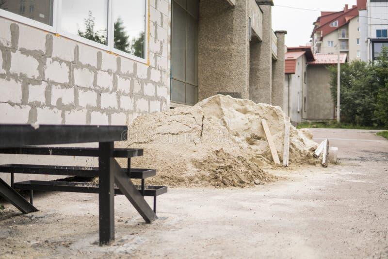 Σωρός της άμμου, τσιμέντο που αναμιγνύεται, χρήση κατά τη διάρκεια της οικοδόμησης στοκ εικόνα