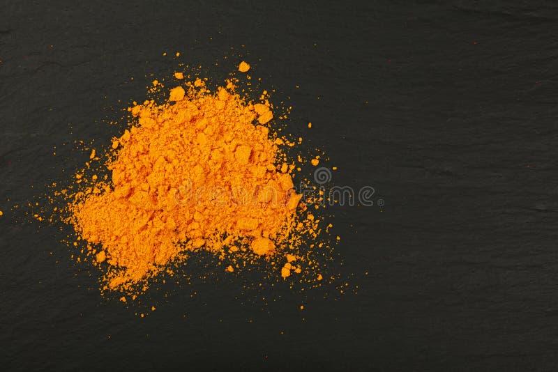Σωρός της κίτρινης turmeric σκόνης στο μαύρο πίνακα πλακών στοκ φωτογραφίες με δικαίωμα ελεύθερης χρήσης
