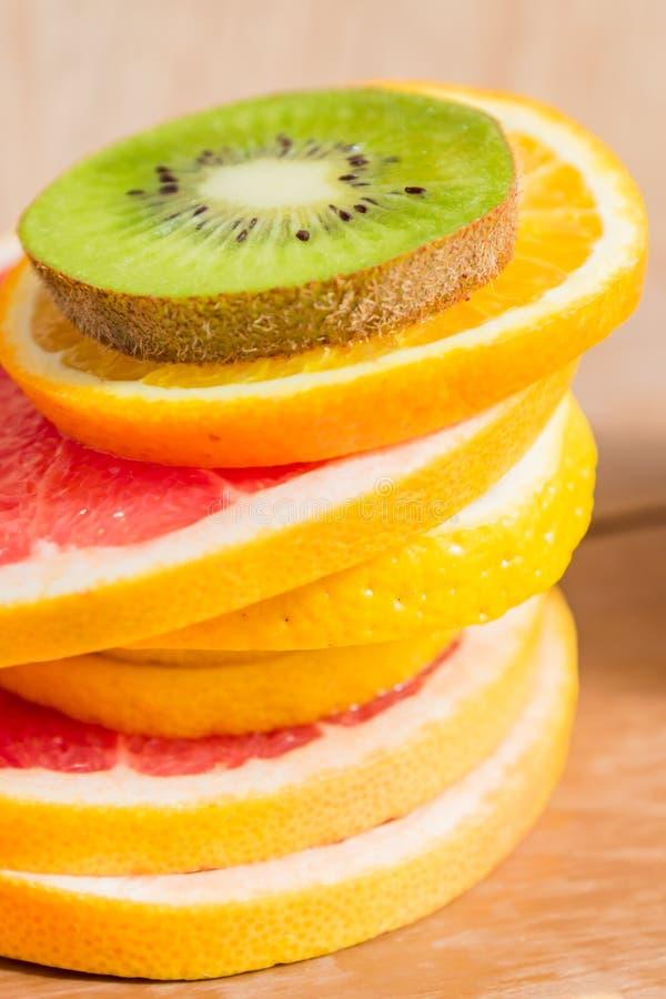Σωρός της φέτας των πορτοκαλιών, λεμόνια, ακτινίδιο, γκρέιπφρουτ στο ξύλινο υπόβαθρο στοκ φωτογραφία