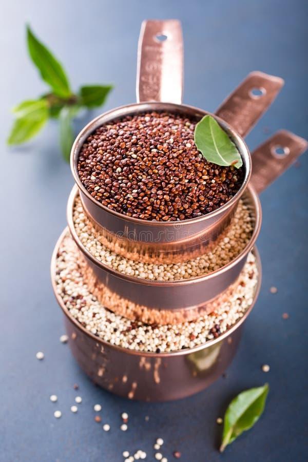 Σωρός του χαλκού τρία που μετρά τα φλυτζάνια με μικτό ακατέργαστο quinoa στοκ εικόνα
