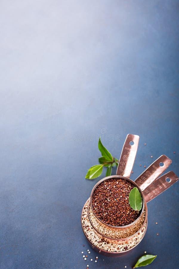 Σωρός του χαλκού τρία που μετρά τα φλυτζάνια με μικτό ακατέργαστο quinoa στοκ φωτογραφία