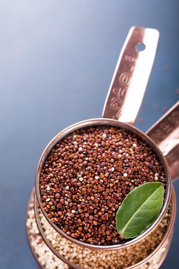 Σωρός του χαλκού τρία που μετρά τα φλυτζάνια με μικτό ακατέργαστο quinoa στοκ εικόνες