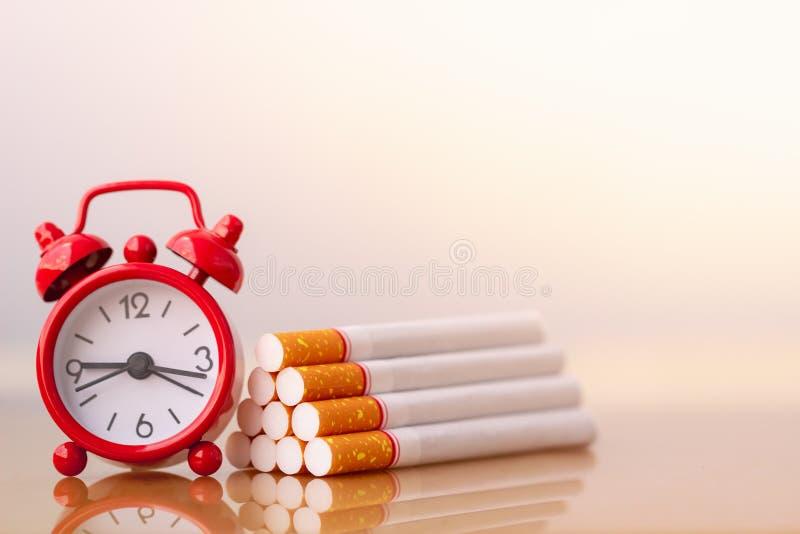 Σωρός τσιγάρων και κόκκινο ξυπνητήρι Κόσμος καμία ημέρα καπνών Αριθμός τσιγάρων και οικογενειών στοκ εικόνες