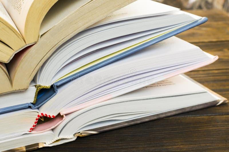 Σωρός των ανοικτών βιβλίων βιβλίων με σκληρό εξώφυλλο σε έναν παλαιό σκοτεινό καφετή ξύλινο πίνακα Εκπαίδευση στοκ φωτογραφία