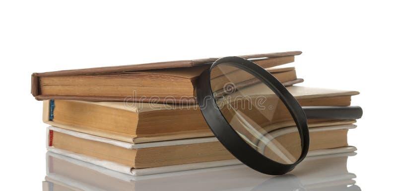 Σωρός των βιβλίων και ένας πιό magnifier σε ένα απομονωμένο λευκό υπόβαθρο βιβλία παλαιά Εκπαίδευση σχολείο μελέτη στοκ φωτογραφίες
