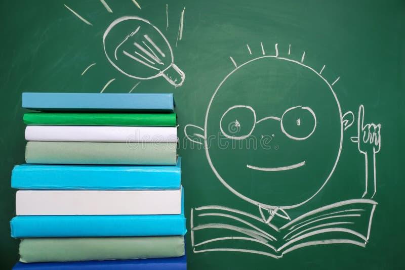 Σωρός των βιβλίων και του συρμένου μαθητή στον πίνακα κιμωλίας στοκ φωτογραφίες με δικαίωμα ελεύθερης χρήσης