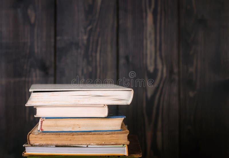 Σωρός των βιβλίων βιβλίων με σκληρό εξώφυλλο στον ξύλινο πίνακα πίσω σχολείο στοκ εικόνες