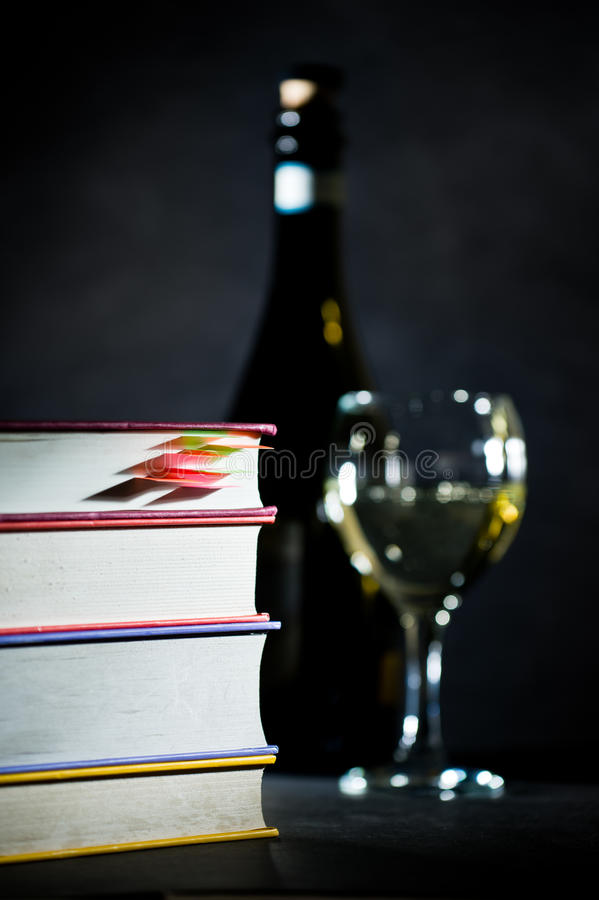 Σωρός των βιβλίων με το γυαλί και μπουκάλι του άσπρου κρασιού στοκ φωτογραφίες με δικαίωμα ελεύθερης χρήσης