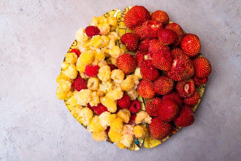 Σωρός των γλυκών φραουλών και των Juicy σμέουρων που απομονώνονται στο υπόβαθρο πετρών Έννοια θερινών υγιής τροφίμων στοκ εικόνες