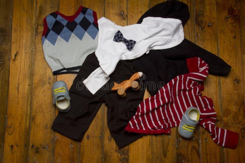 Σωρός των ενδυμάτων εξαρτήσεων αγοράκι στο ξύλινο υπόβαθρο grunge: onesie, πουλόβερ, παντελόνι, παπούτσια και παιχνίδι στοκ φωτογραφίες με δικαίωμα ελεύθερης χρήσης