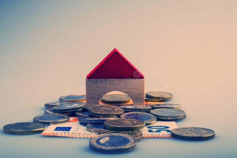 Σωρός των ευρο- νομισμάτων και των λογαριασμών εγγράφου και ένα σχεδιάγραμμα σπιτιών σε ένα φως στοκ φωτογραφία
