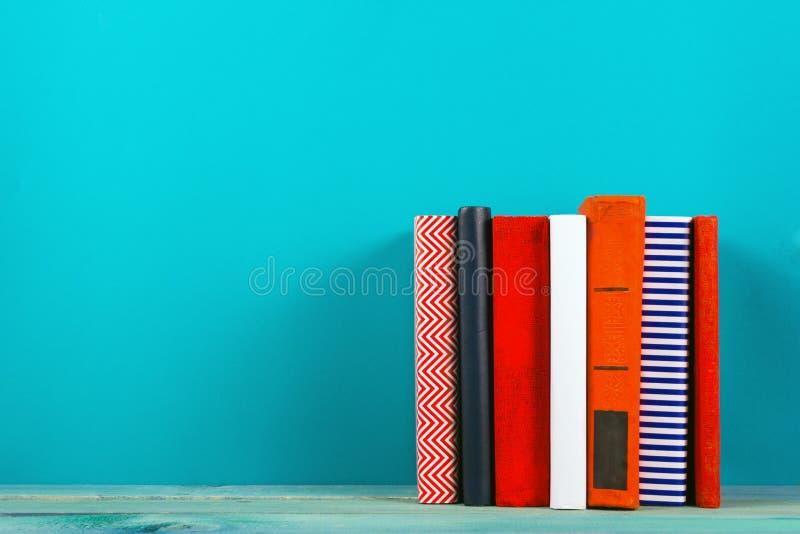Σωρός των ζωηρόχρωμων βιβλίων, βρώμικο μπλε υπόβαθρο, ελεύθερο διάστημα αντιγράφων στοκ εικόνα με δικαίωμα ελεύθερης χρήσης
