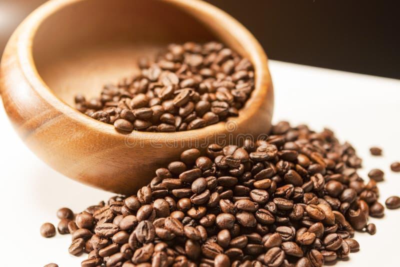 Σωρός των καφετιών ψημένων φασολιών καφέ στο ξύλινο κύπελλο σε άσπρο Surfa στοκ φωτογραφίες