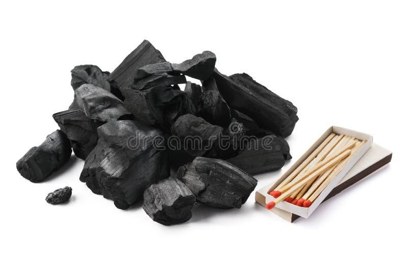 Σωρός των κομματιών ξυλάνθρακα και ένα κιβώτιο των αντιστοιχιών   στοκ φωτογραφίες