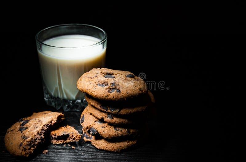 Σωρός των μπισκότων τσιπ σοκολάτας και ποτήρι του γάλακτος στο σκοτεινό ξύλινο υπόβαθρο στοκ εικόνες με δικαίωμα ελεύθερης χρήσης
