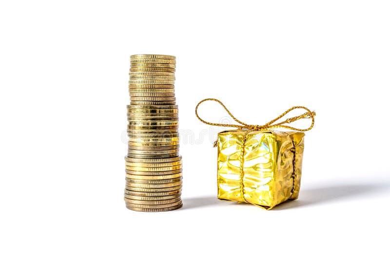 Σωρός των νομισμάτων δίπλα σε ένα χρυσό κιβώτιο δώρων που απομονώνεται σε ένα λευκό στοκ φωτογραφίες