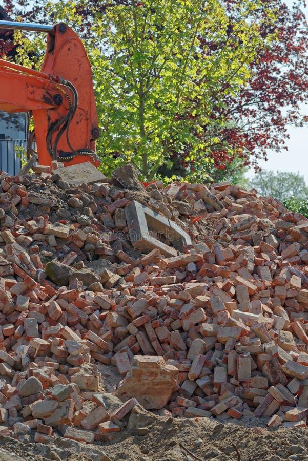 Σωρός των παλαιών τούβλων και του υδραυλικού βραχίονα εκσκαφέων εκσακαφέων στο υπόβαθρο στοκ φωτογραφία με δικαίωμα ελεύθερης χρήσης