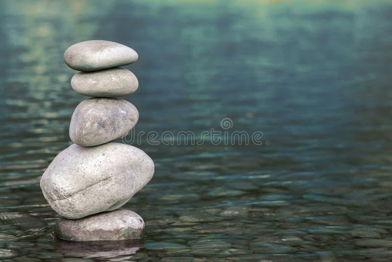 Σωρός των πετρών που ισορροπούν στην κορυφή στο μπλε νερό του ποταμού στοκ εικόνα με δικαίωμα ελεύθερης χρήσης