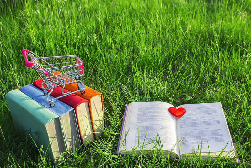 Σωρός των πολύχρωμων παλαιών βιβλίων και του ανοικτού βιβλίου στη χλόη στη φύση, μικρό κάρρο, υπαίθριο γραφείο στοκ φωτογραφίες