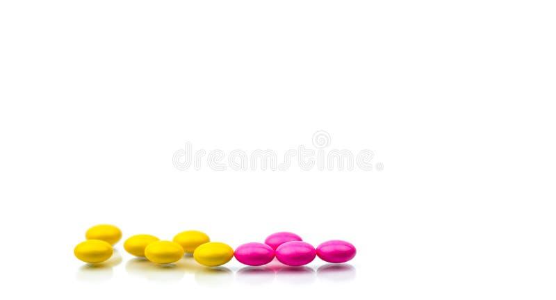 Σωρός των ρόδινων και κίτρινων στρογγυλών ζαχαρωμένων χαπιών ταμπλετών που απομονώνονται στο άσπρο υπόβαθρο με το διάστημα αντιγρ στοκ εικόνα με δικαίωμα ελεύθερης χρήσης