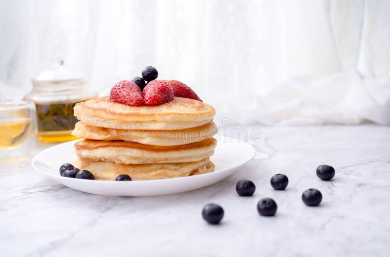 Σωρός των τηγανιτών με το κάλυμμα, τη φράουλα και το βακκίνιο Τοποθετημένος σε ένα άσπρο πιάτο σε ένα μαρμάρινο διάστημα πινάκων  στοκ εικόνες με δικαίωμα ελεύθερης χρήσης