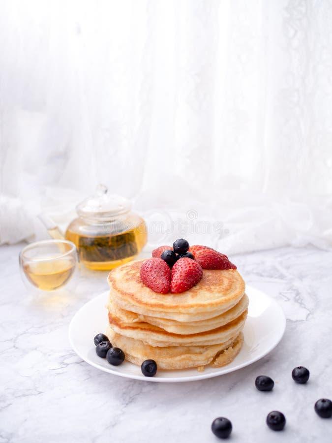 Σωρός των τηγανιτών με το κάλυμμα, τη φράουλα και το βακκίνιο Τοποθετημένος σε ένα άσπρο πιάτο σε ένα μαρμάρινο διάστημα πινάκων  στοκ εικόνα με δικαίωμα ελεύθερης χρήσης