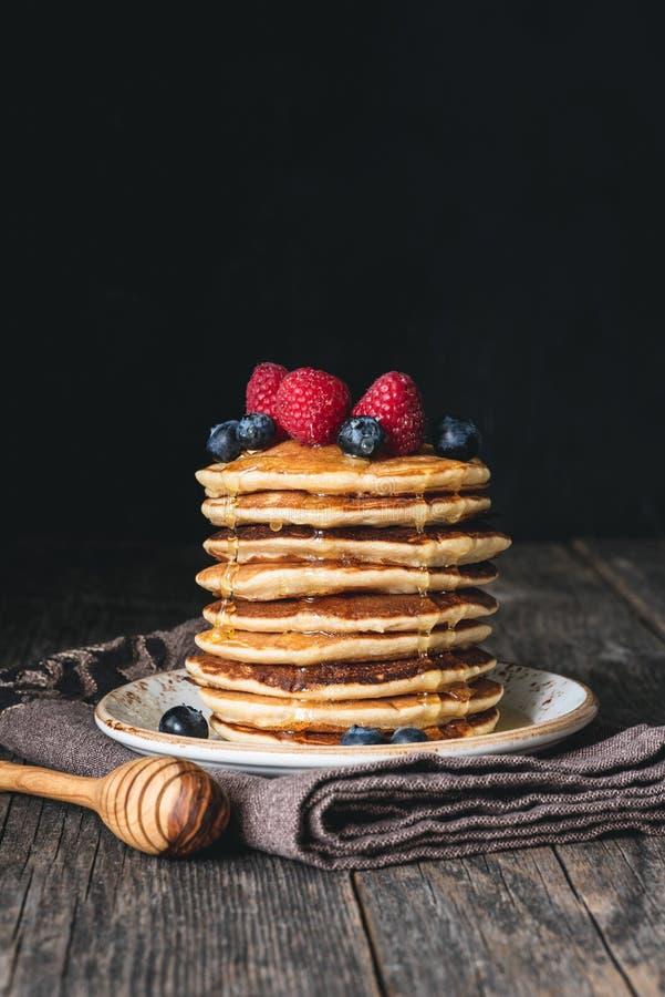 Σωρός των τηγανιτών με το μέλι και των φρέσκων μούρων στον ξύλινο πίνακα στοκ εικόνες με δικαίωμα ελεύθερης χρήσης