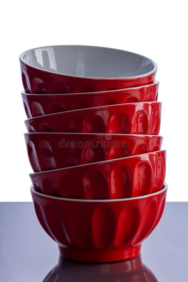 Σωρός των φωτεινών κόκκινων ramekins σε έναν πίνακα κουζινών στοκ φωτογραφία