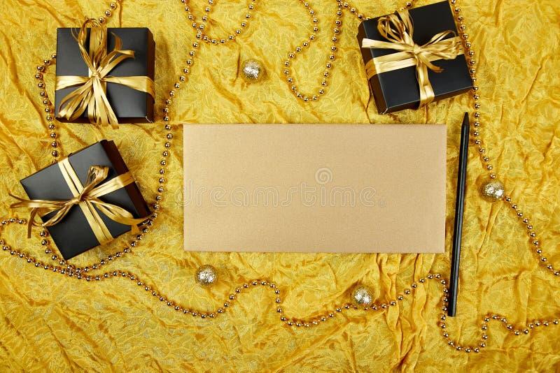 Σωρός των χειροποίητων κιβωτίων δώρων πολυτέλειας μαύρων με τη χρυσή διακόσμηση κορδελλών DIY, κενό έγγραφο φύλλων για το κείμενο στοκ φωτογραφία