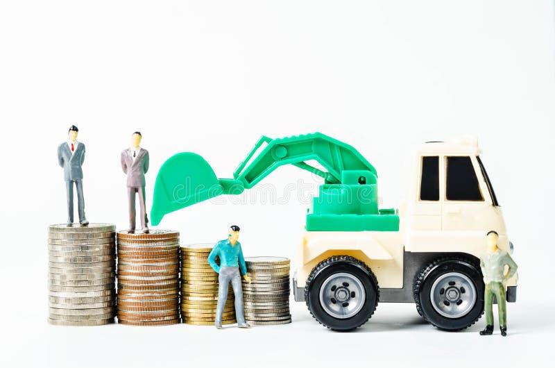 Σωρός των χρημάτων νομισμάτων και backhoe του παιχνιδιού φορτωτών με το επιχειρησιακό άτομο mi στοκ εικόνα