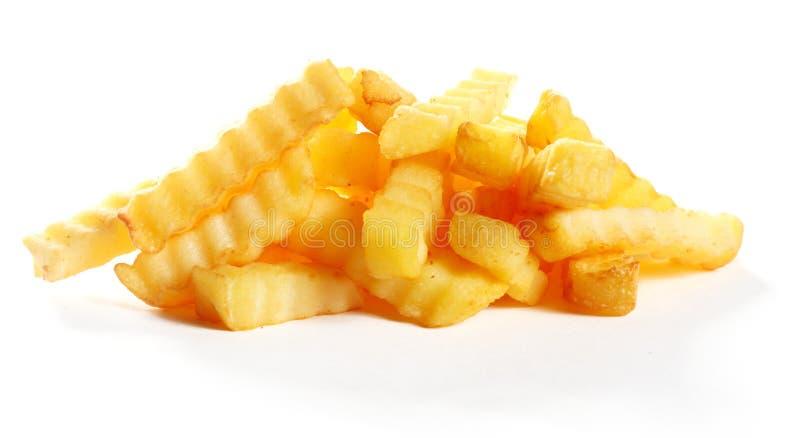 Σωρός των χρυσών τηγανισμένων crinkle τσιπ πατατών περικοπών στοκ εικόνα με δικαίωμα ελεύθερης χρήσης