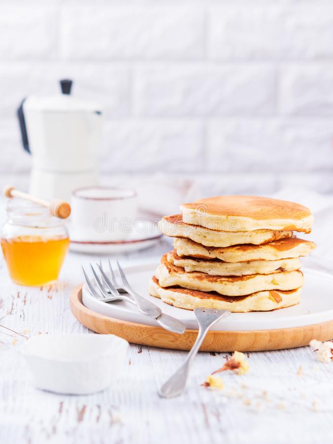 Σωρός χρυσού - εύγευστες τηγανίτες, μέλι, coffe στο άσπρο υπόβαθρο με το διάστημα αντιγράφων Ρομαντικό πρόγευμα και παραδοσιακός στοκ εικόνες